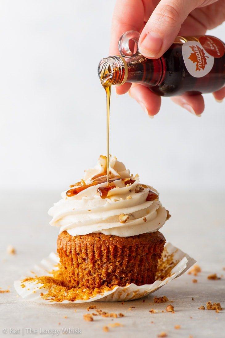 Drizzling the vegan cupcake with maple syrup.