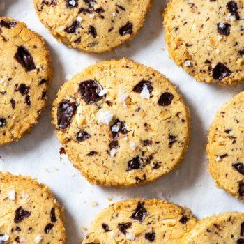 Overhead view of chocolate hazelnut slice and bake cookies, sprinkled with flaky sea salt.
