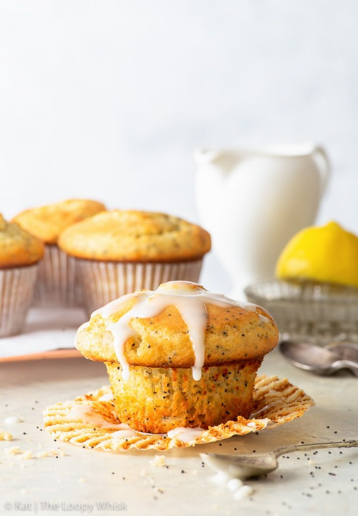 A gluten free lemon poppy seed muffin drizzled with lemon icing in the foreground, with the muffin wrapper partially unwrapped. More muffins are in the background.