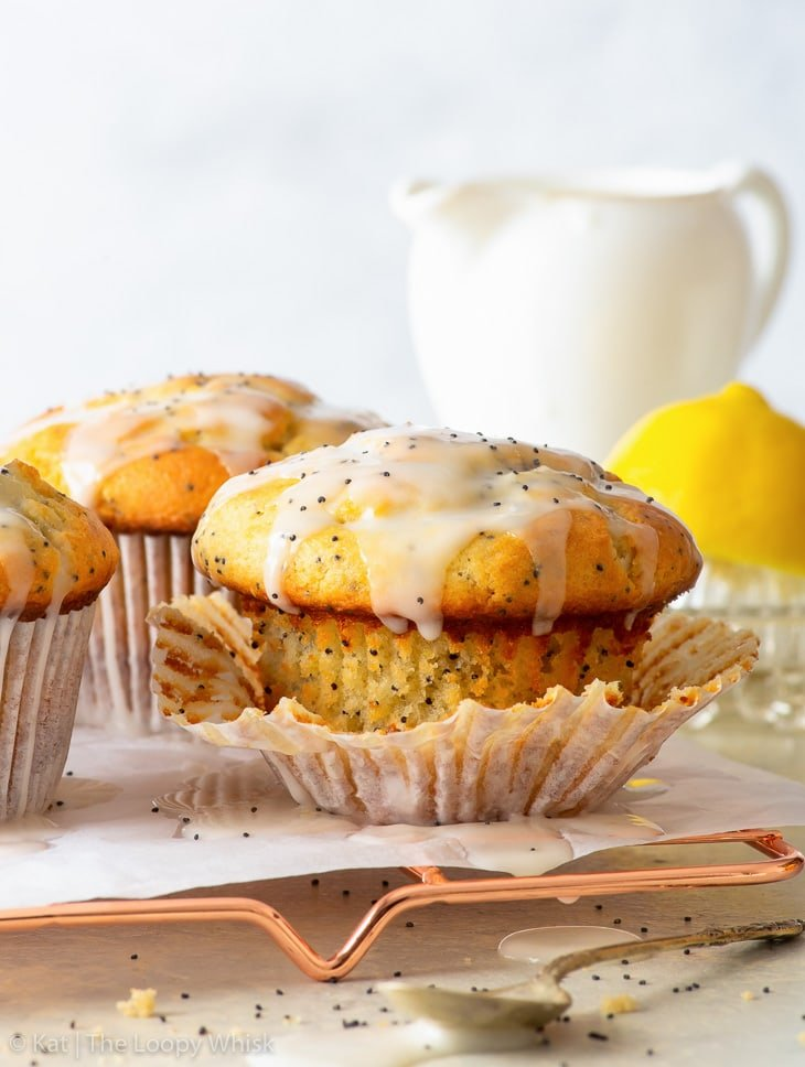 Lemon poppy seed muffins on a copper wire cooling rack.