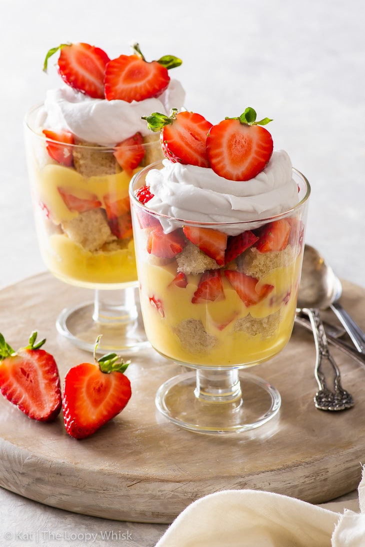 Two vegan strawberry lemonade trifles decorated with fresh berries on a wooden platter.