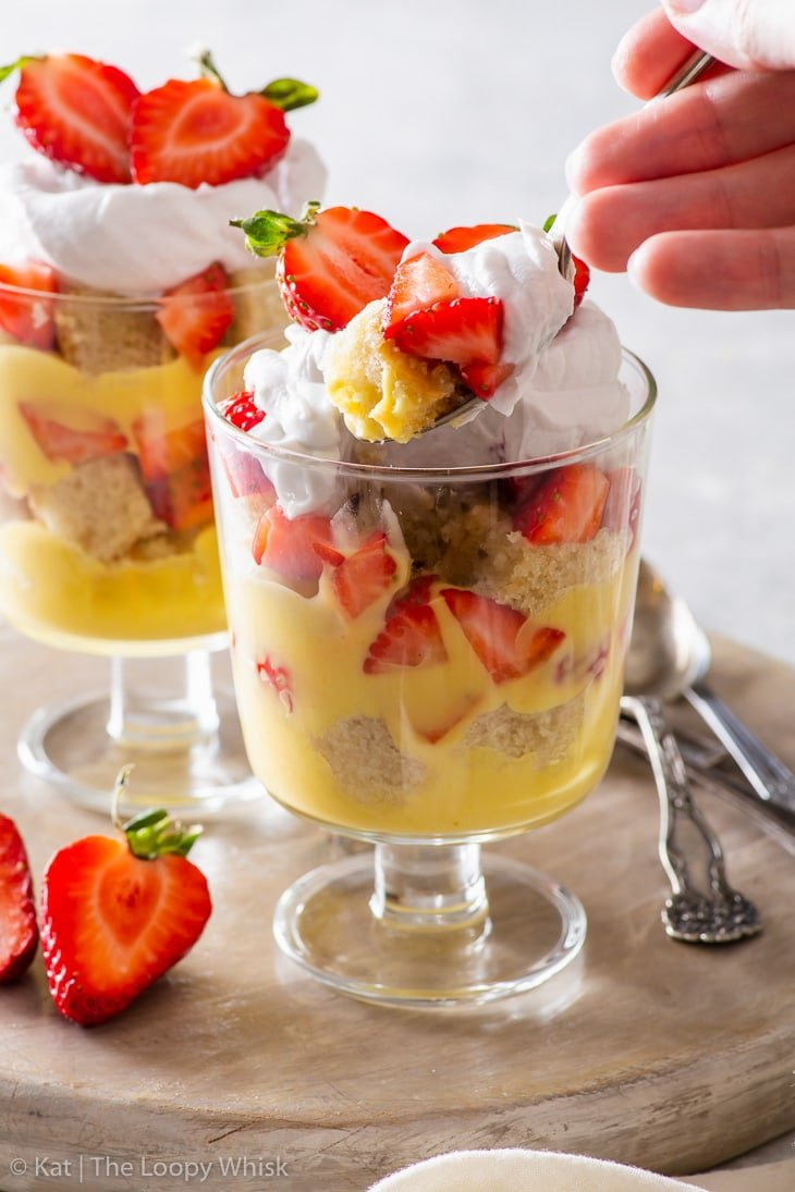 Scooping a spoonful of the trifle with a dessert spoon.