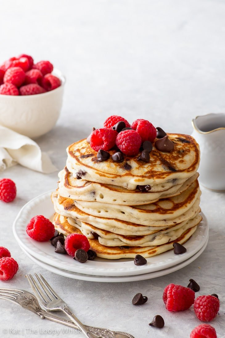 A tall stack of chocolate chip pancakes, topped with extra chocolate chips and raspberries.