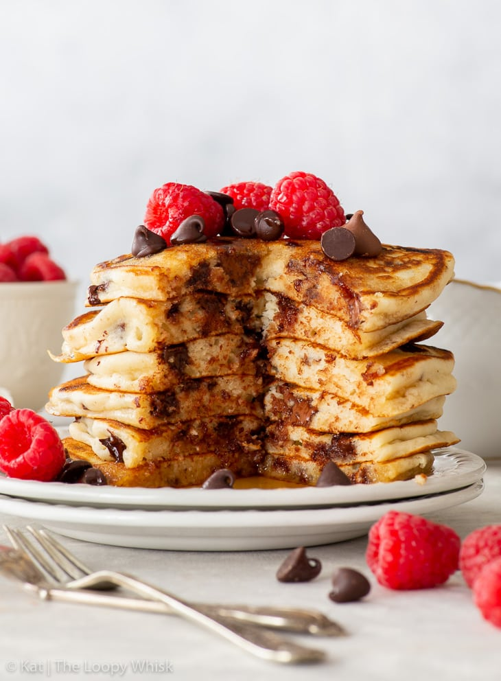 A tall stack of chocolate chip pancakes, topped with extra chocolate chips and raspberries. A wedge was cut out from the stack, exposing the fluffy texture.