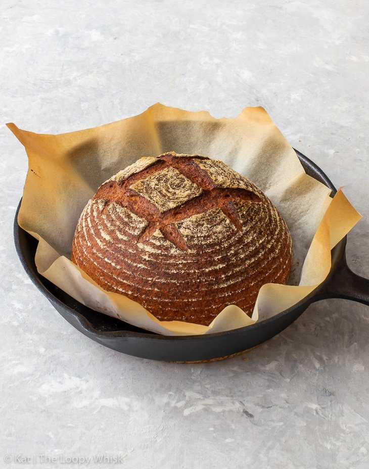 A baked, golden brown loaf of gluten free bread in a cast iron skillet.