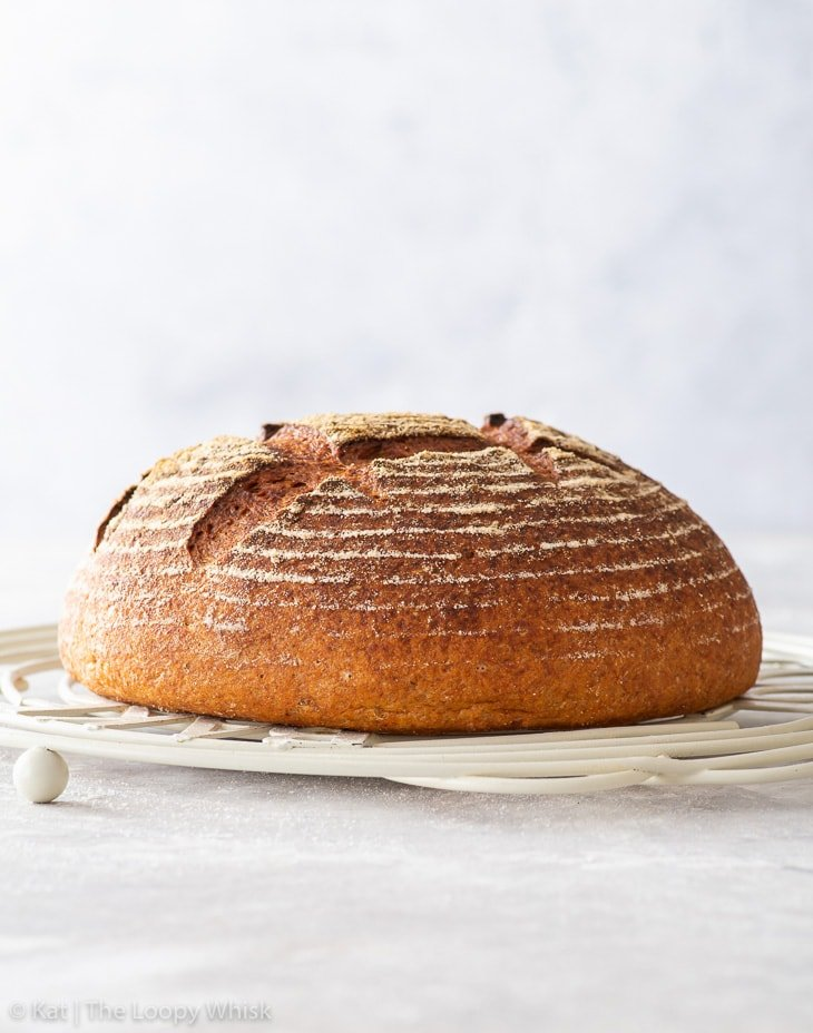 A baked, golden brown loaf of bread on a white wire cooling rack.