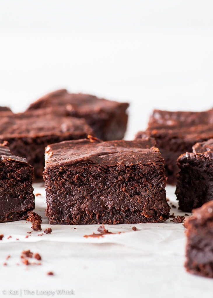Fudgy vegan chocolate brownies on a piece of white parchment paper.