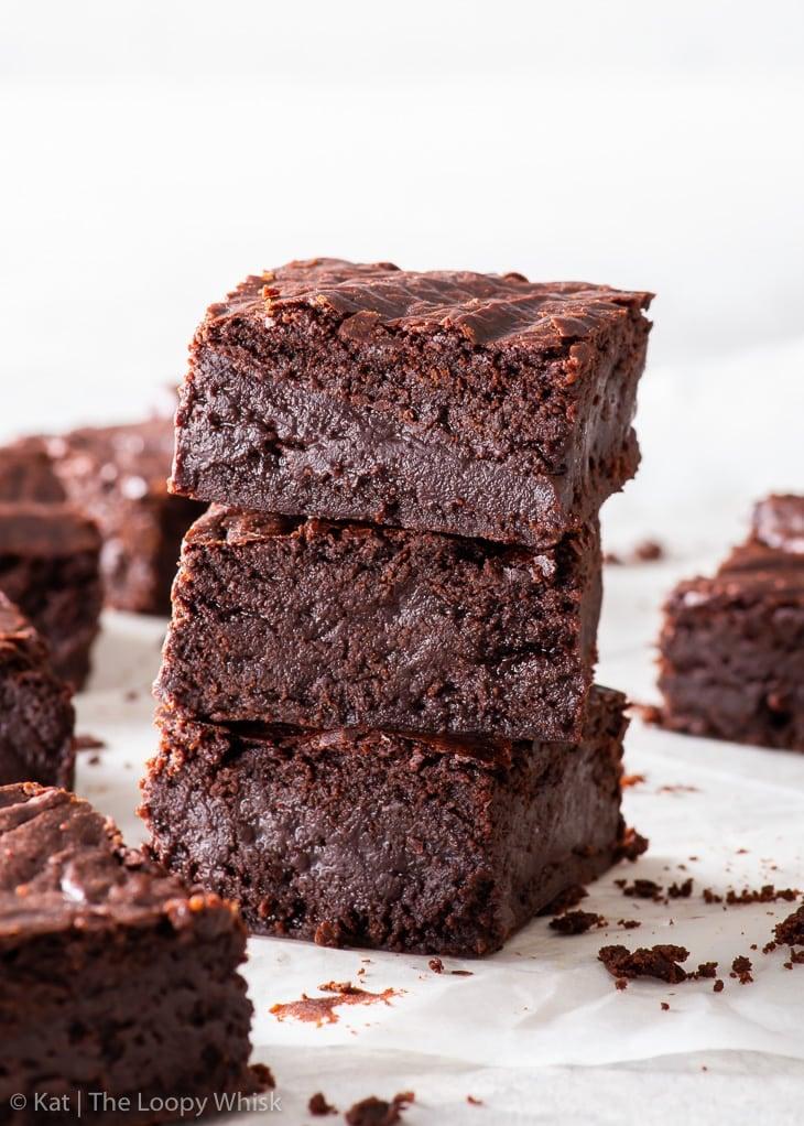 A stack of three fudgy vegan chocolate brownies.