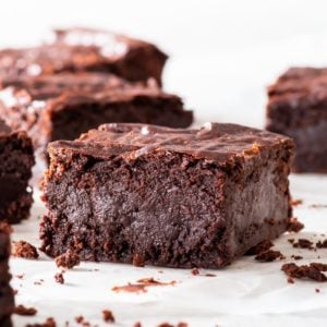 Fudgy vegan chocolate brownie on a piece of white parchment paper.