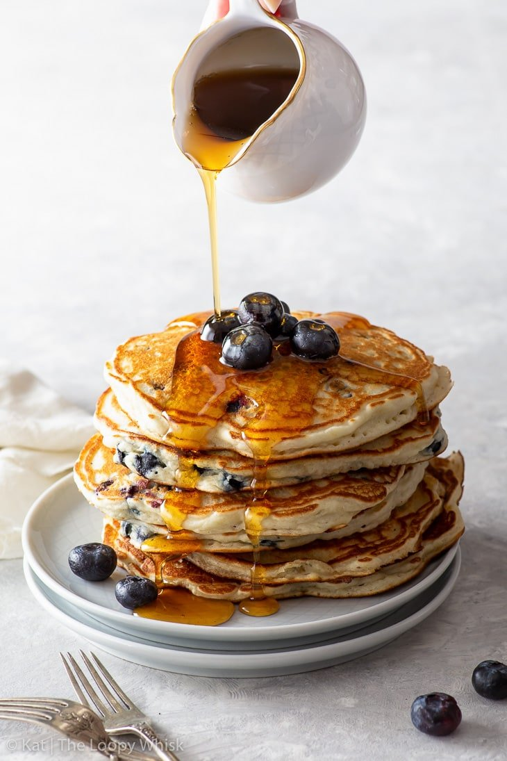 A stack of fluffy blueberry pancakes with maple syrup being poured over them.