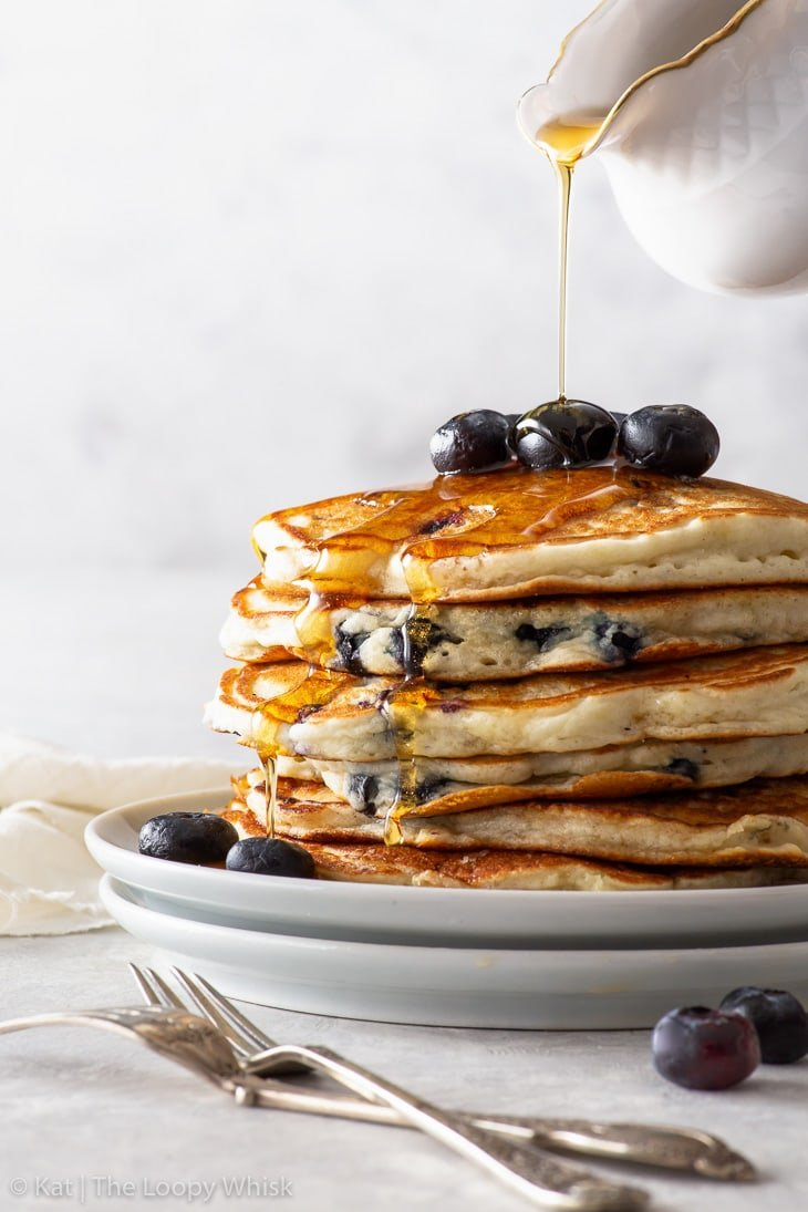 A stack of fluffy gluten free blueberry pancakes with maple syrup being poured over them.