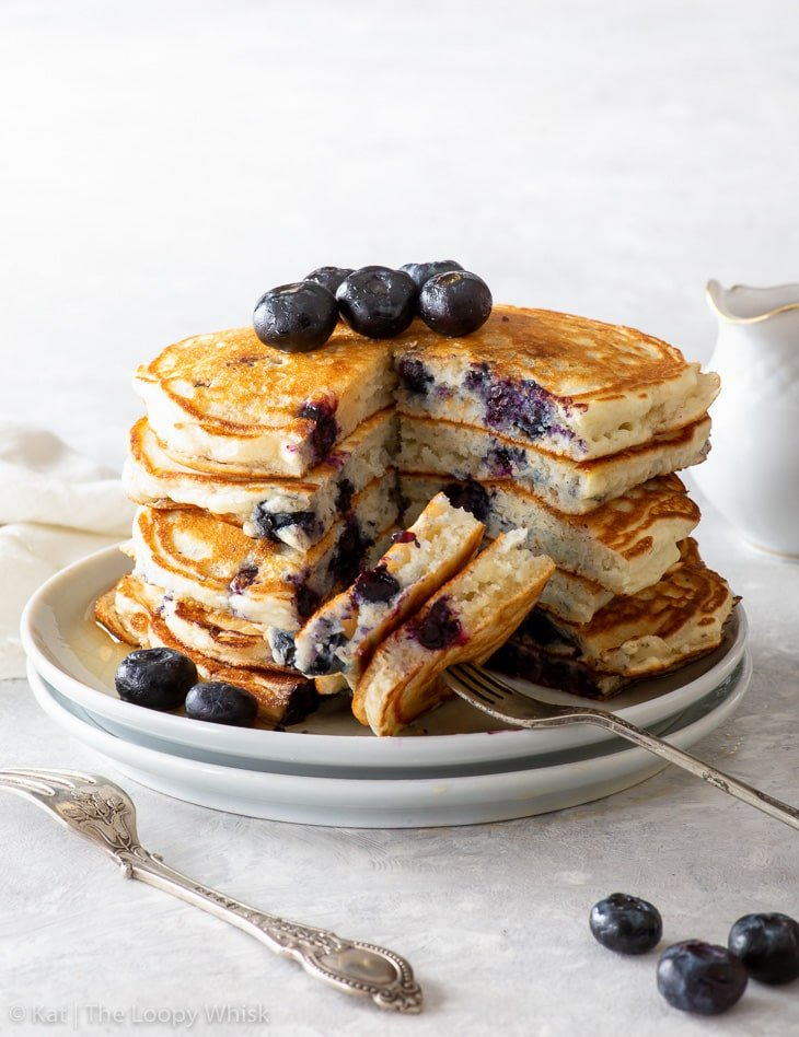 A stack of fluffy blueberry pancakes. A wedge was cut out from the stack, exposing the fluffy texture.