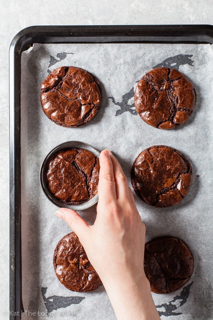 The process of correcting the shape of the brownie cookies with a round cookie cutter.