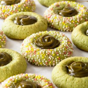 Vegan matcha thumbprint cookies, with a matcha sauce centre, on a sheet of white parchment paper.