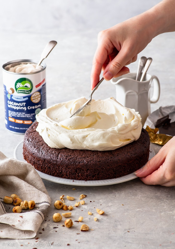 Spreading whipped coconut cream on top of the hazelnut chocolate sponge.