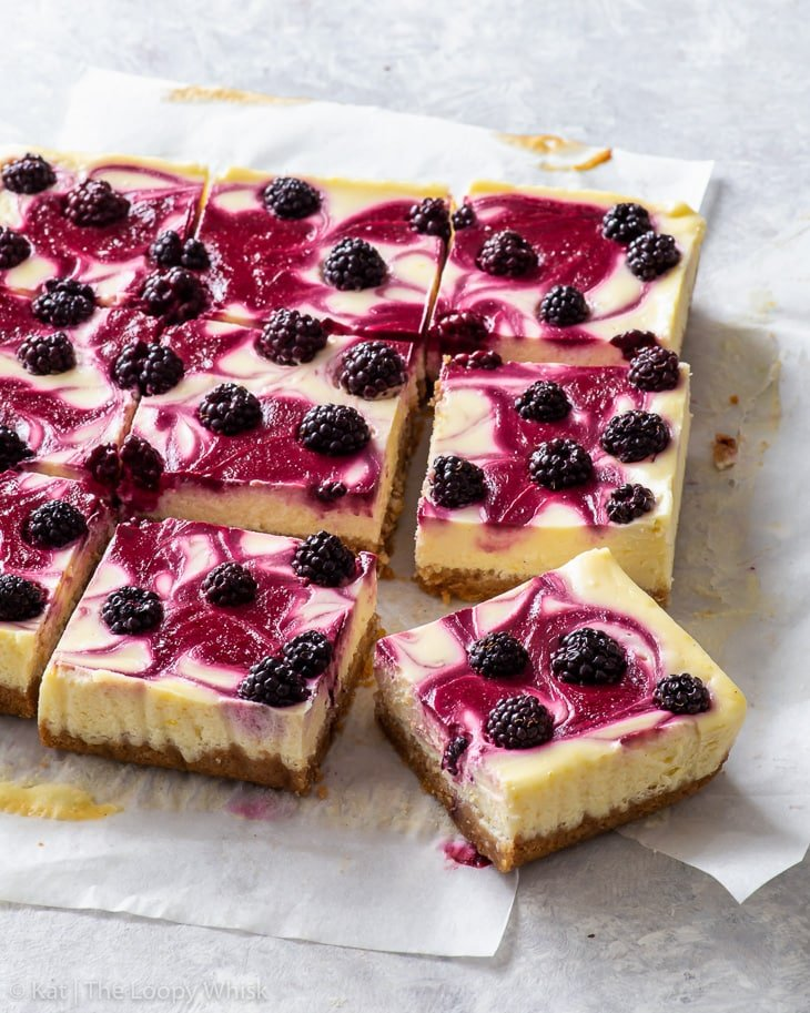 Cut blackberry cheesecake bars on a piece of parchment paper.