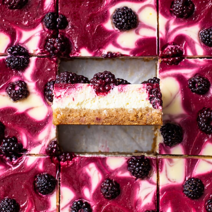 Overhead view of the cut blackberry cheesecake bars, with one positioned vertically.
