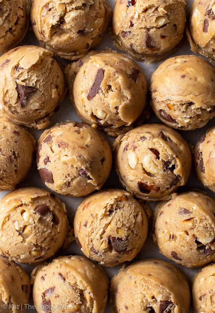 Scoops of hazelnut milk chocolate chip cookies, arranged closely together in neat rows.