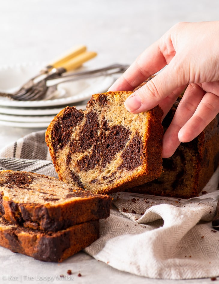 A hand holding a slice of the marbled banana bread.
