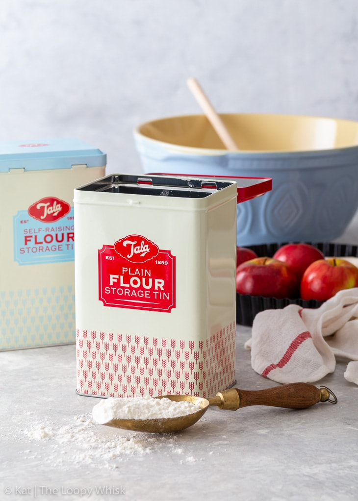 Flour storage tins on a white wooden surface, with a mixing bowl and a few apples in the background.