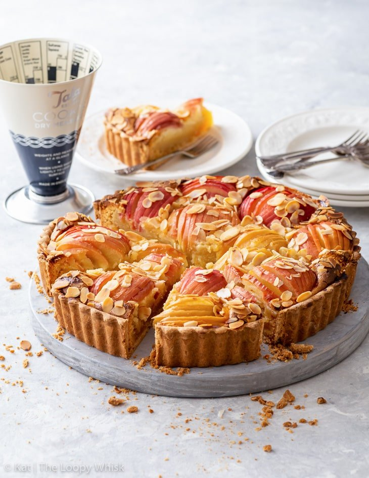 Apple tart with a few pieces cut on a round wooden board.