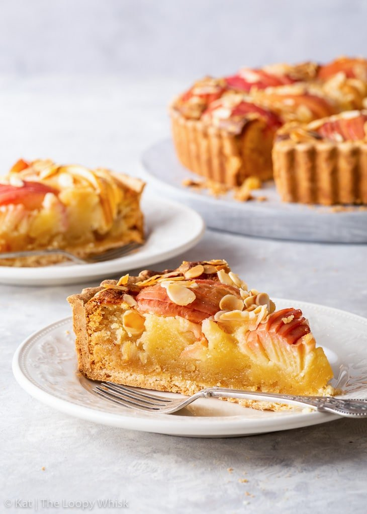 A slice of apple frangipane tart on a dessert plate, with another piece and the rest of the tart in the background.