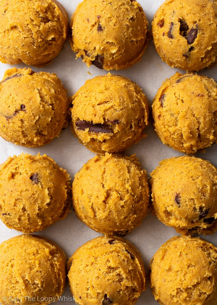 Overhead view of pumpkin chocolate chip cookie dough scoops on white parchment paper.