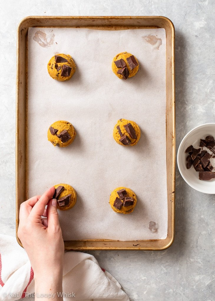 Placing chopped chocolate on top of cookie dough scoops before baking.