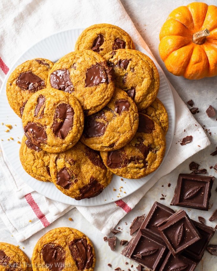 Pumpkin chocolate chip cookies on a white plate, with a small pumpkin and chopped chocolate next to it.