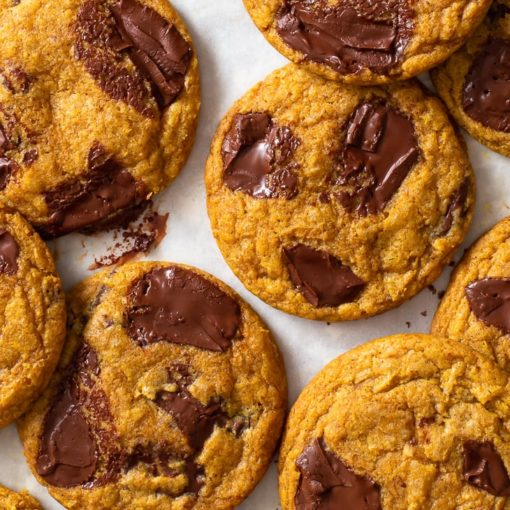 Overhead view of pumpkin chocolate chip cookies on white parchment paper.
