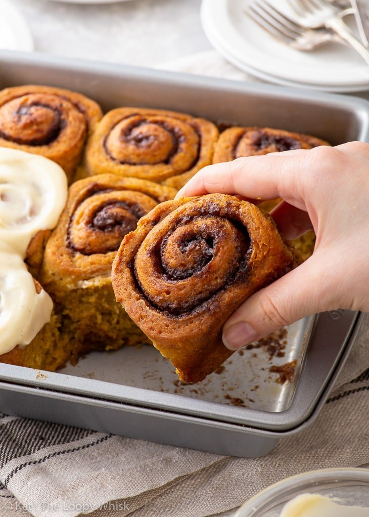 A hand taking a gluten free pumpkin cinnamon roll out of the baking tin.