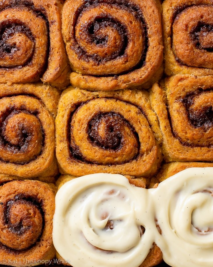 Overhead view of the gluten free pumpkin cinnamon rolls, two of which are topped with maple cream cheese icing.