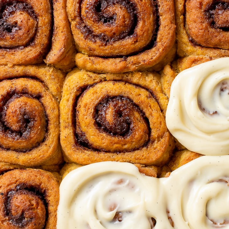 Overhead view of the gluten free pumpkin cinnamon rolls, three of which are topped with maple cream cheese icing.