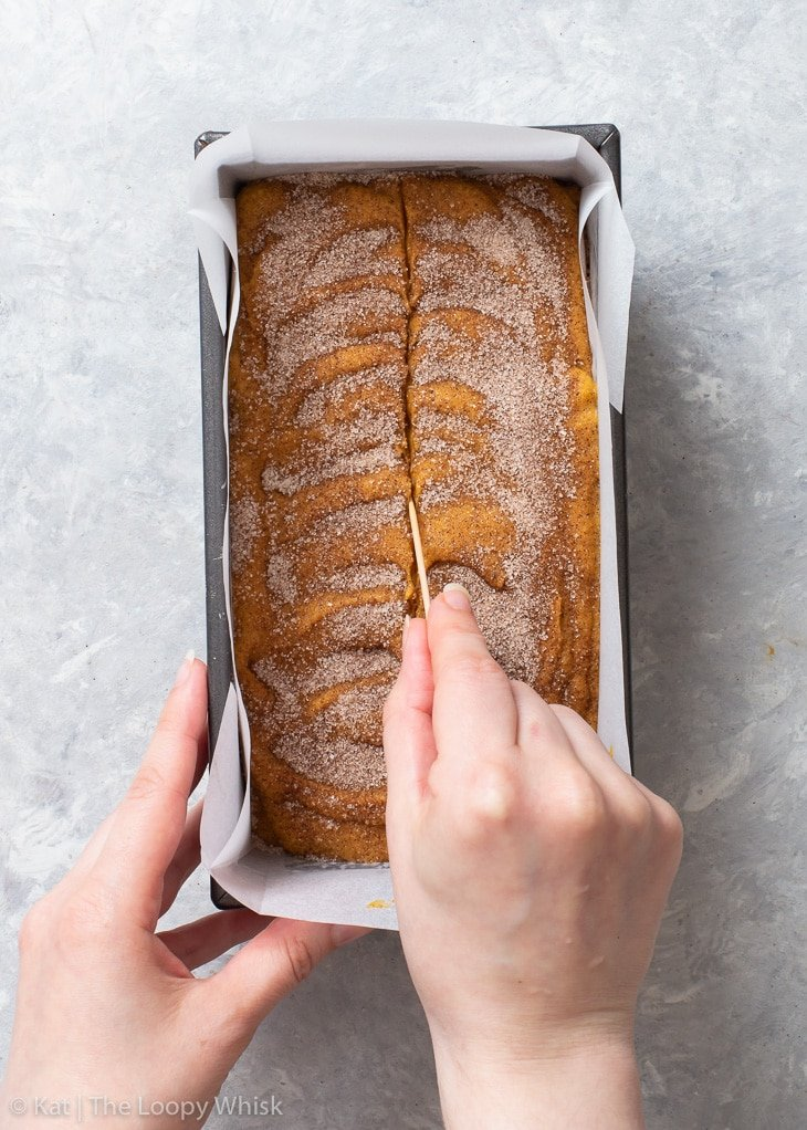 Using a toothpick to draw a line down the middle of pumpkin bread batter before baking.