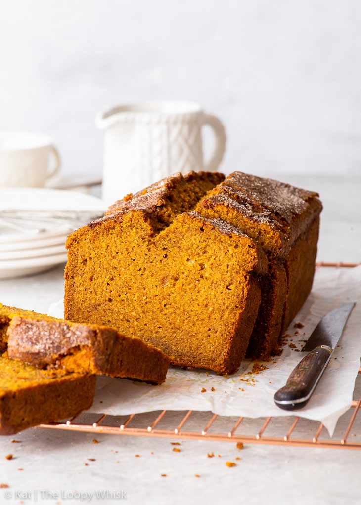 Gluten free pumpkin bread on a copper wire cooling rack, with a few pieces cut.