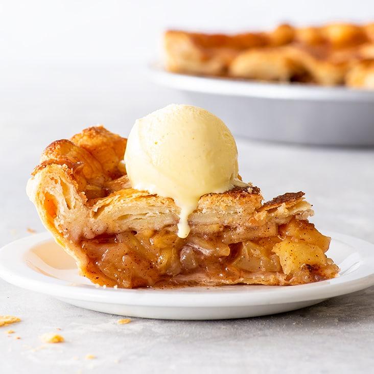 A piece of apple pie topped with a scoop of ice cream on a white plate.