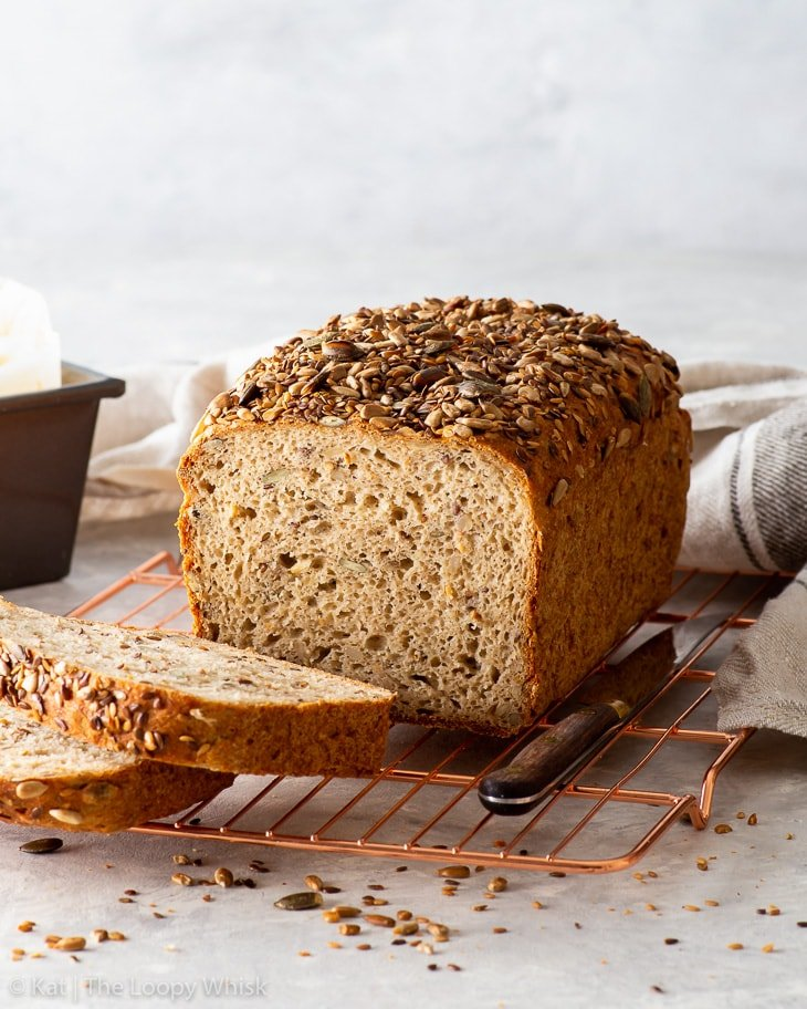 A loaf of mixed seed bread on a copper wire cooling rack, with a few pieces already cut.