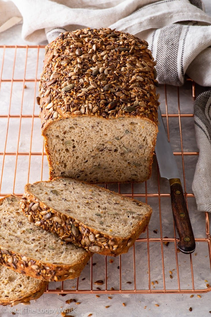 Gluten free seeded loaf on a copper wire cooling rack.