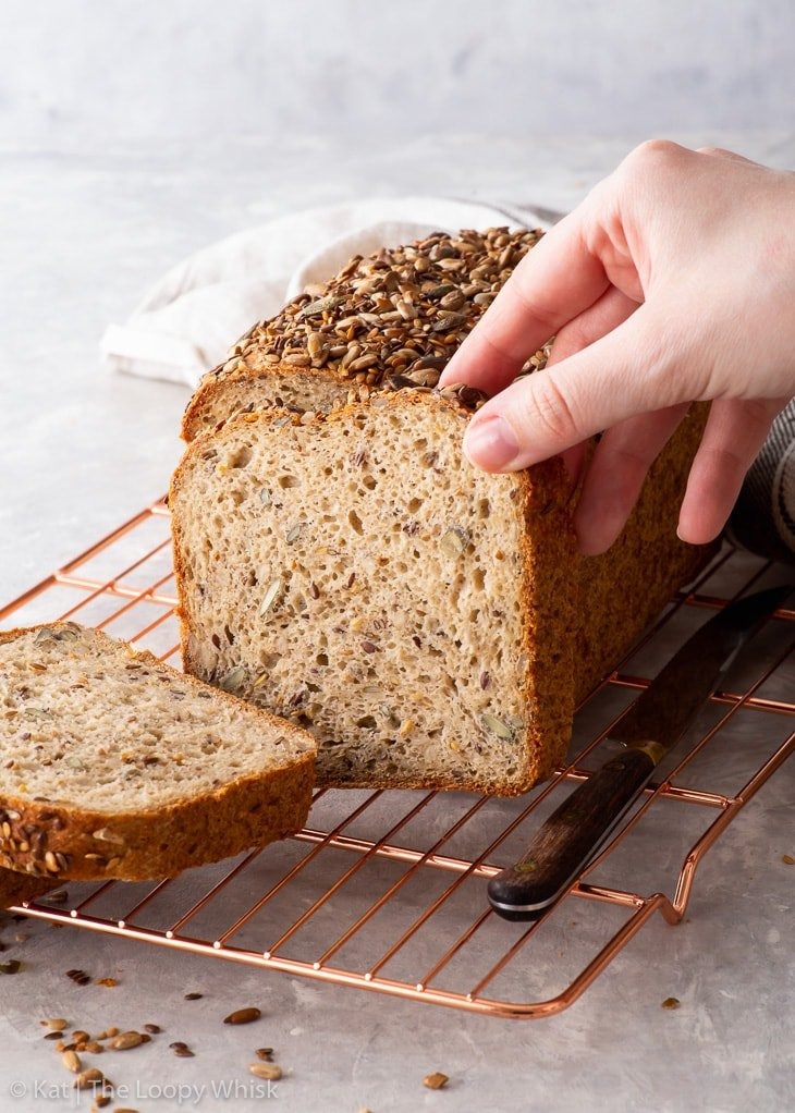 A hand holing a piece of gluten free seeded loaf.