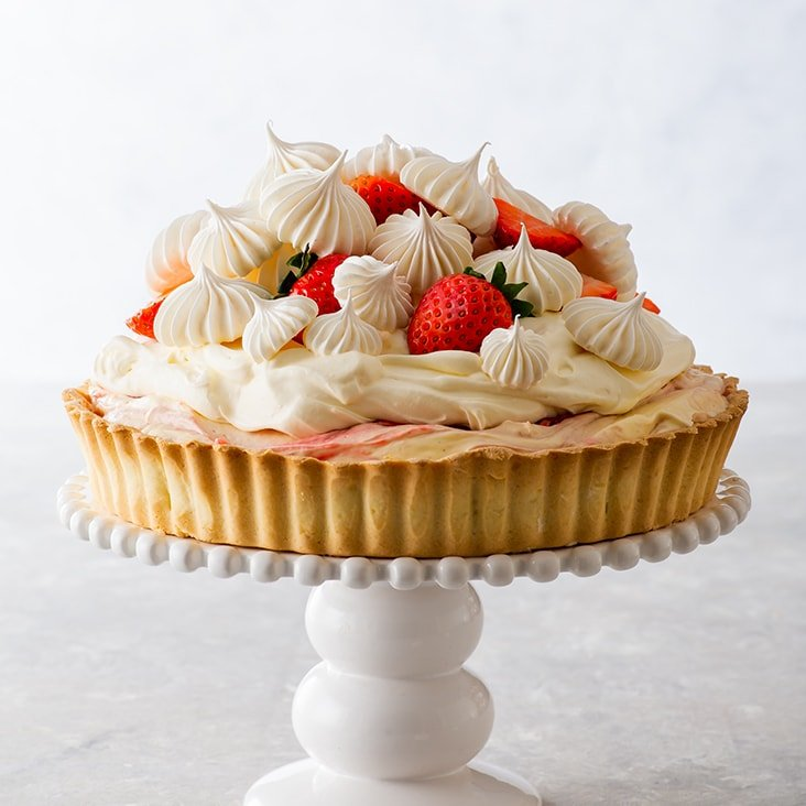 Decorated strawberries and cream tart on a white ceramic cake stand.