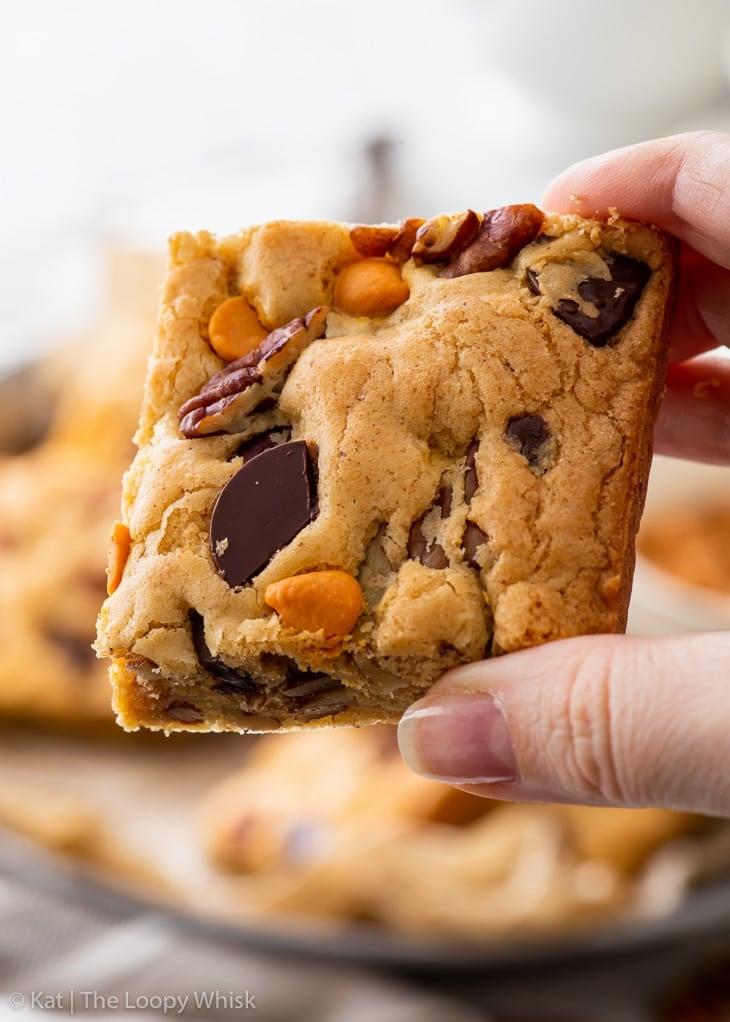 A hand holing a brown butter, pecan & butterscotch cookie bar.