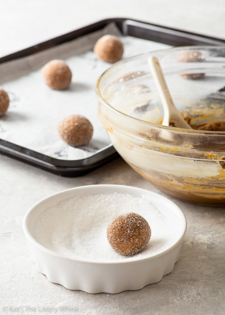 The process of rolling molasses cookie dough balls in granulated sugar before baking.