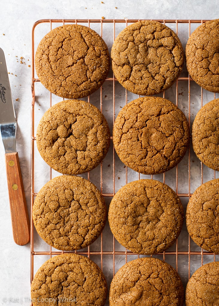 Overhead view of molasses cookies on a copper wire cooling rack, with a small offset spatula next to them.