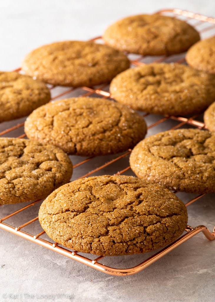 Gluten free molasses cookies on a copper wire cooling rack.