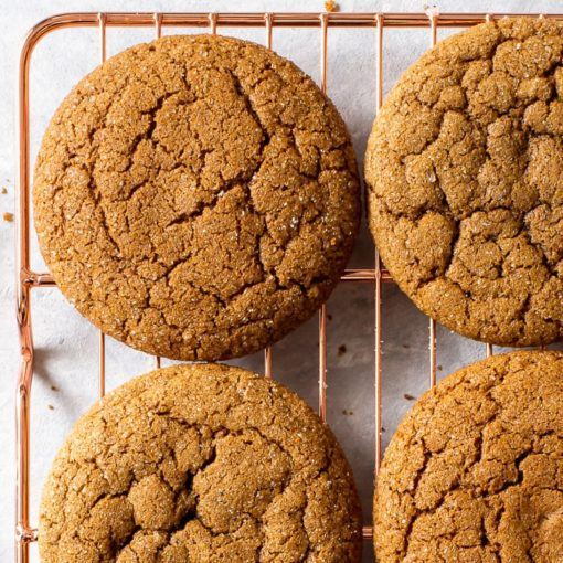 Overhead view of molasses cookies on a copper wire cooling rack.
