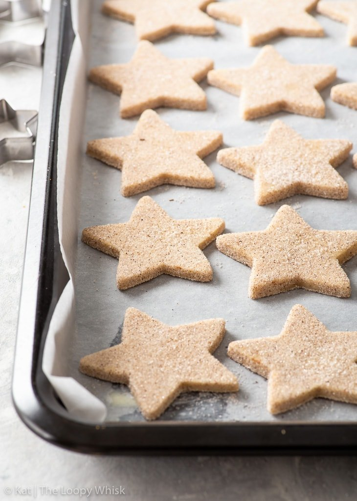 Star-shaped shortbread cookies arranged on a lined baking sheet.
