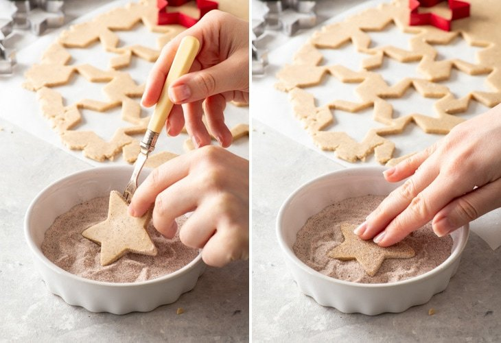 Rolling the star-shaped shortbread cookies in a cinnamon-sugar mixture before baking.