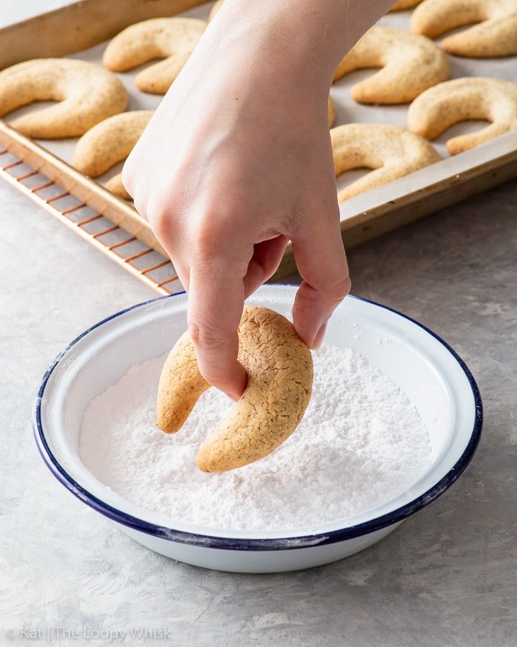 The process of rolling vanillekipferl in powdered sugar.