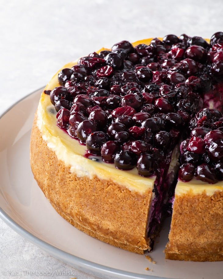 Blueberry cheesecake on a white and grey large serving plate.