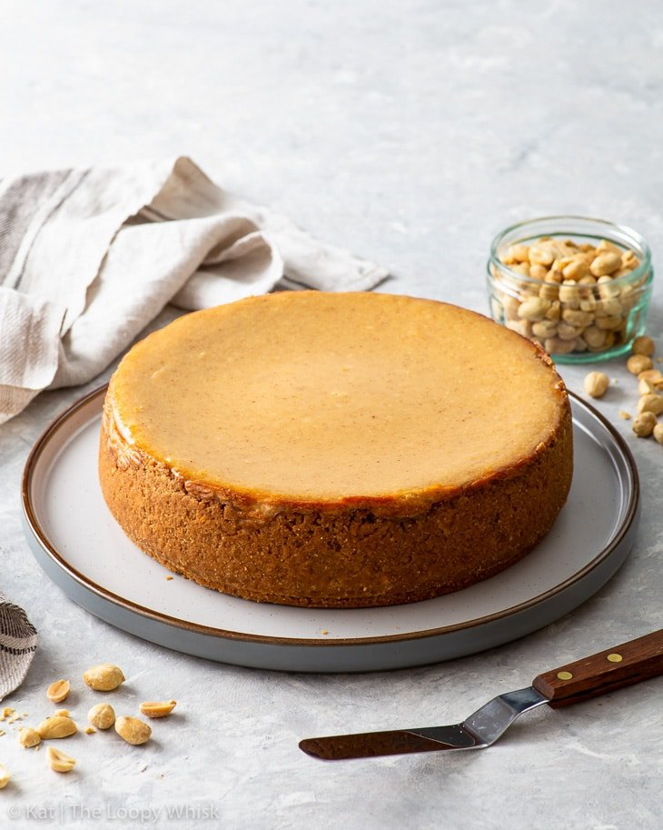The baked peanut butter cheesecake on a large round serving plate.